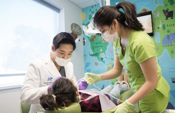 Image shows Dr. Tommy conducting a pediatric dental exam.